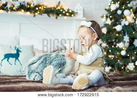 Little girl sitting with a hare on the background of trees. Merry Christmas.