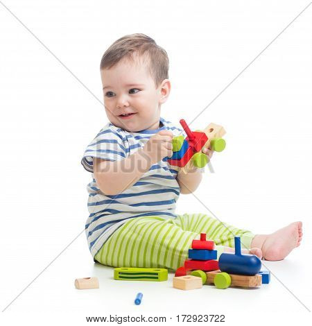 Baby boy playing with blocks toys looking away in surprise