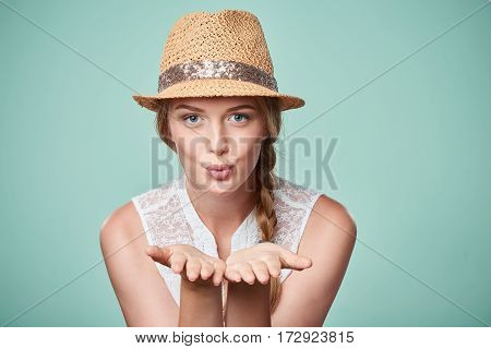 Beautiful woman wearing summer straw fedora hat blowing a kiss