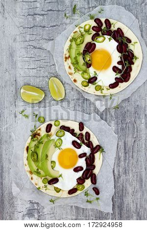Mexican huevos rancheros tacos. Breakfast tostadas with black beans avocado fried egg microgreens sriracha ketchup. Top view flat lay copy space
