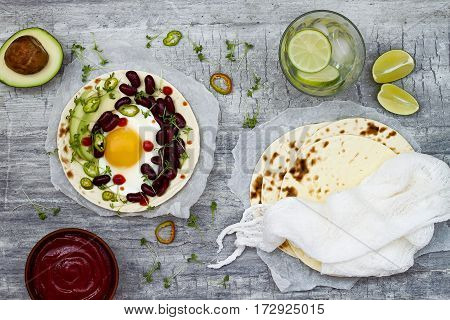 Mexican huevos rancheros tacos. Breakfast tostadas with black beans avocado fried egg microgreens sriracha ketchup.Top view flat lay copy space
