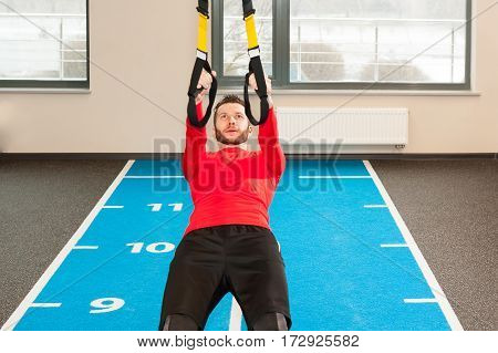 white curly bearded sporty man exercising with fitness straps in gym