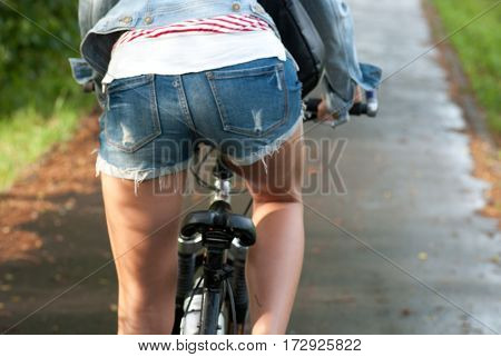 Close-up of rear view of a pretty woman in denim blue shorts on bicycle at under bright sun day. selective focus macro soft shot with shallow DOF.