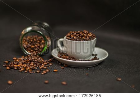 aromatic coffee beans in a white cup and spilled coffee beans from an overturned jar artistic decoration