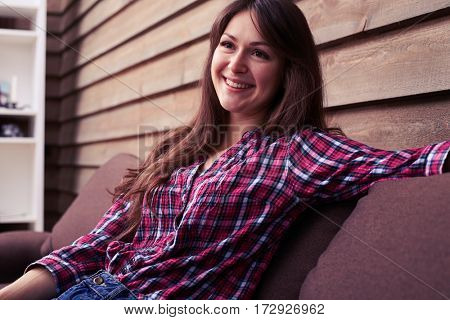 Side view of positive girl enjoying good time at home. Lovely girl spending time at home while sitting on the sofa. Pretty girl wearing checked shirt and jeans leaning on the settee