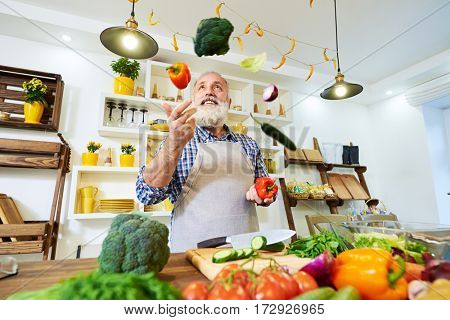 Low angle of male chef wearing a cooking apron juggling with colorful vegetables. Trying to prepare a nutritious dinner. Man prepares ingredients, standing in the kitchen