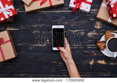 High angle of isolated female hand holding smartphone with black screen. Telephone isolated over grunge wooden flat lay background