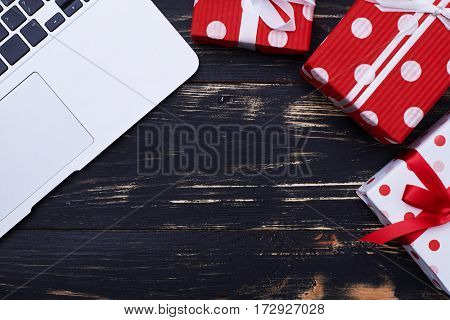 Top view of the laptop with three gift boxes over grunge flat lay background