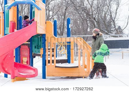 Mother and children in snow at playground
