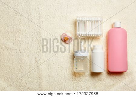 Baby's accessories and cosmetics on fabric background, top view