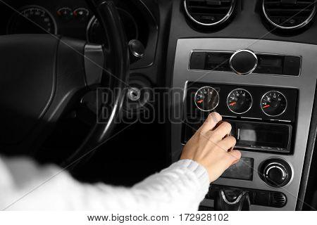 Closeup of woman driving car and tuning radio