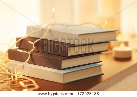 Pile of books and beautiful garland on night table, closeup