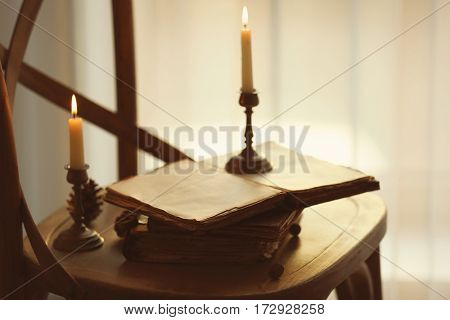 Old books and candles on wooden chair