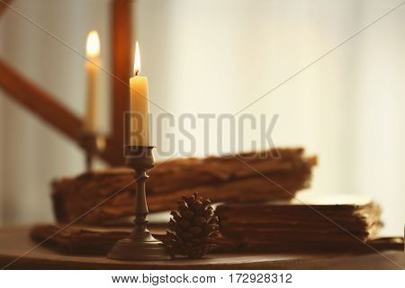 Candle, cone and old books on wooden chair, closeup