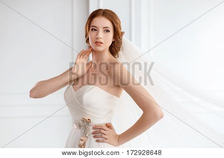 Bride in white dress and long veil indoors. Young gorgeous fashion model posing in white interior studio's room near big windon. Portrait shot