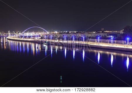Dubai Water Canal and Arch Bridge illuminated at night. United Arab Emirates Middle East