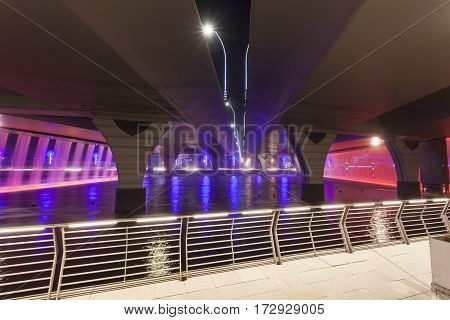 Dubai Water Canal and Waterfall under the Sheikh Zayed Road bridge at night. United Arab Emirates Middle East
