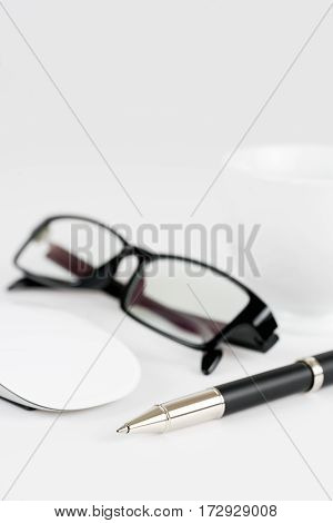 cup of coffee pen mouse and glasses on a white background