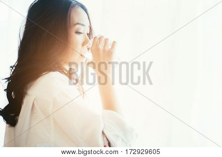 Asian Woman Drinking Water On Window View In The Morning Sun
