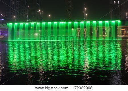 Green illuminated Waterfall at the Sheikh Zayed Bridge part of the Dubai Water Canal. Dubai United Arab Emirates Middle East