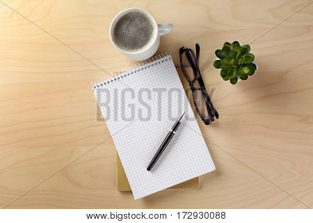 Notebook, cup of coffee and eyeglasses on wooden table