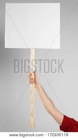 Male hand holding blank banner on wooden stick against light background