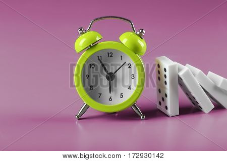 Dominoes and alarm clock on color background