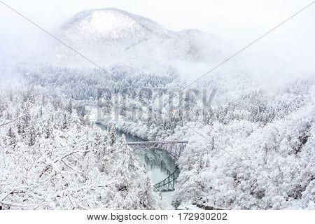Bridge on a river with snow mountain as background in Tadami Fukushima Japan.