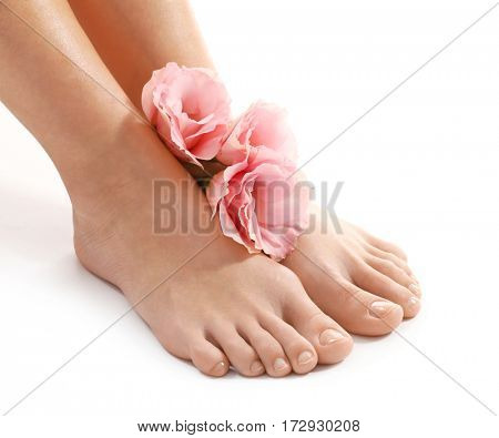 Female legs with flowers on white background