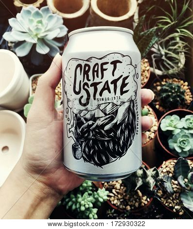 Hand holding craft state beer can with houseplants background
