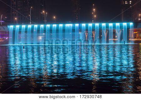 Blue illuminated Waterfall at the Sheikh Zayed Bridge part of the Dubai Water Canal. Dubai United Arab Emirates Middle East