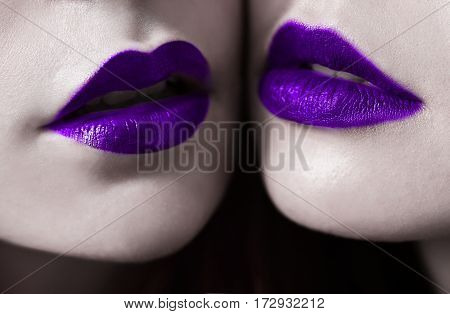 Female lips with violet blueberry matte lipstick closeup. Macro photo lips. Girls lesbians. Blue lips