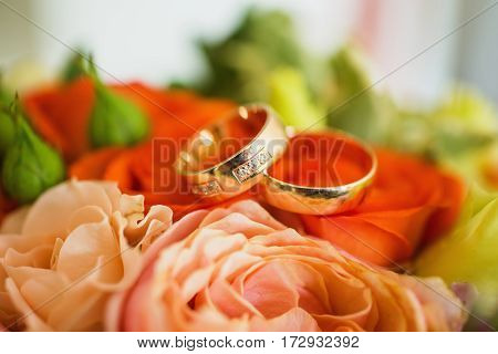 Wedding rings on red flowers background wedding bands infinity sign of the rings