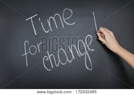 Female hand writing phrase TIME FOR CHANGE on blackboard