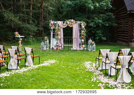 Beautiful wedding ceremony outdoors. Decorated chairs stand on the grass. Wedding arch made of cloth and white and pink flowers on a green natural background. Old doors rustic style. Wedding in rustic style. Wedding concept