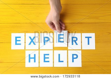 Female hand and phrase EXPERT HELP on wooden background