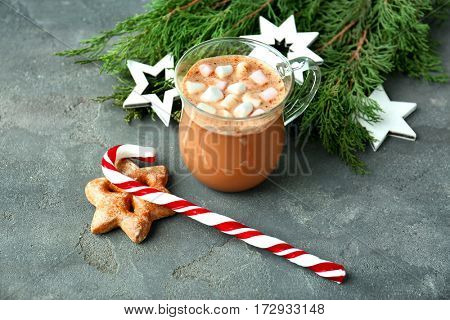 Christmas composition with candy cane, cup of coffee and decorations on grey table