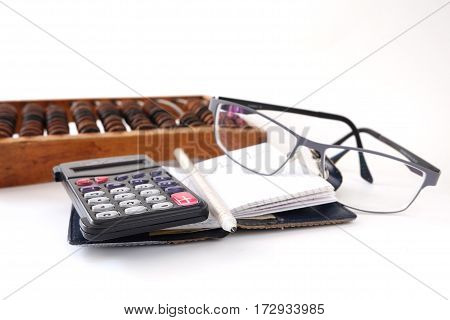 calculator glasses pencils white background old scores