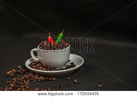 aromatic coffee beans in white cup with decoration of acute red and green chili peppers spilled coffee beans artistic decoration