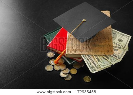 School supplies, graduation hat, dollar banknotes and coins on blackboard. Pocket money concept