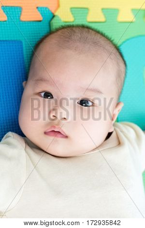 Portrait Of A Little Adorable Newborn Infant Baby Girl Lying On Back On Colorful Eva Foam And Lookin