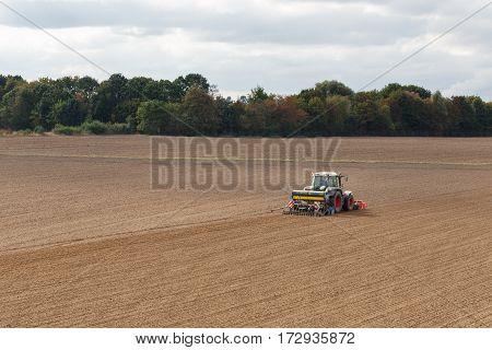 Farmer seeding crops at field in spring