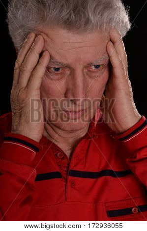 sad older man in red on a black background