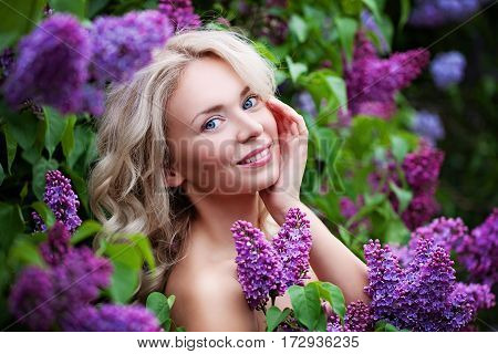 Spa Model Woman with Healthy Skin and Blonde Hair on Flowers Background. Spring Beauty Facial Treatment and Cosmetology Concept