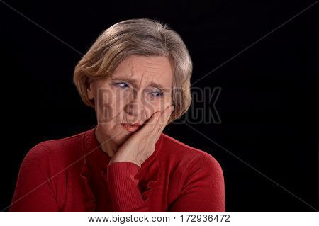 melancholy senior woman in red on a black background