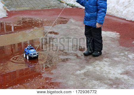 Spring. The snow is melting. The image of a child dressed in a jacket boots gloves. A child plays on the Playground with toy car: the car driven through a puddle on the rope.