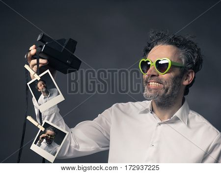 Heart shaped glasses wearing man with instant camera take selfie retro color toned