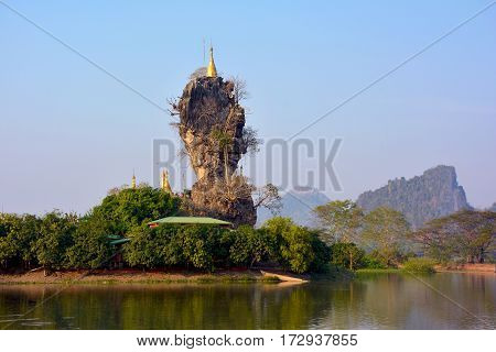 Kyauk Kalap (Kyaut Ka Lat) Pagoda in Hpa-An, Myanmar. Mount Zwegabbin in the background