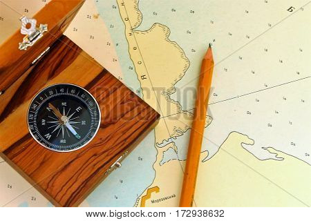 Conceptual image of a magnetic compass and pencil lying on a map for plotting a journey geocaching or orienteering where it is used as a navigational instrument