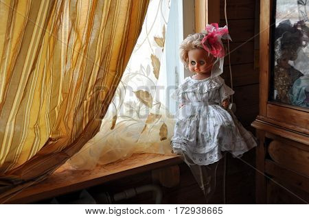 Big doll in a smart white dress and with a bow in her hair sitting on a wooden window sill. Russia